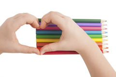 Child hands form a heart shape above color pencils Stock Images