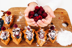 Child hands full of fresh raspberry, top view Royalty Free Stock Photo