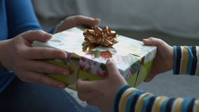 Child hands giving holiday gift box to his mother. Closeup of little boy`s hands giving a gift box wrapped with golden ribbon to his mom on Mother`s Day. Loving