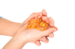 Child hands holding fish oil capsules Stock Photography