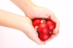 Child hands holding red matt christmas balls Stock Image