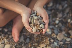 Child hands holding stones on beach sea side waterfront with focus on spa summer vacation on coast travelling. Child hands holding stones on beach sea side Royalty Free Stock Image