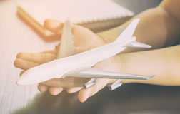 Child hands is holding a white airplane toy Royalty Free Stock Image