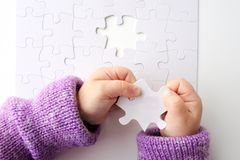 Child hands holds the last puzzle piece of a Jigsaw puzzle Stock Photography