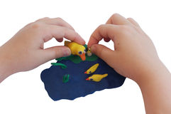 Child hands make a plasticine composition Royalty Free Stock Photos