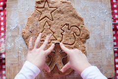Child hands making from dough gingerbread man for Royalty Free Stock Images