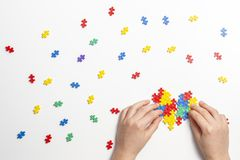 Child hands making multicolored heart on white background. Top view royalty free stock image