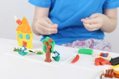 Child hands molding bright house, lowers from plasticine Royalty Free Stock Image