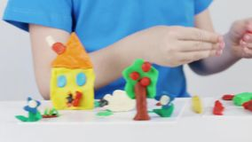 Child hands molding bright house, tree, flowers from plasticine on table. In room stock video