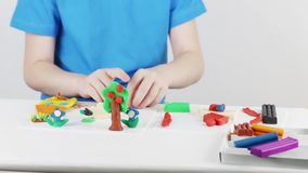 Child hands molding house, tree, flowers from plasticine on table. In room stock video
