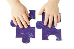 Child hands ond puzzle Royalty Free Stock Images