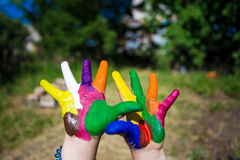 Child hands painted in bright colors isolated on summer nature background Royalty Free Stock Photo