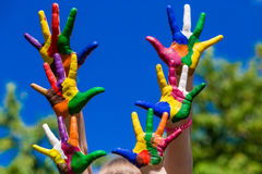 Child hands painted in bright colors isolated on summer nature background Royalty Free Stock Image