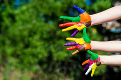 Child hands painted in bright colors isolated on summer nature background Royalty Free Stock Photography