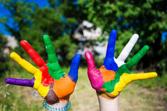 Child hands painted in bright colors isolated on summer nature background Stock Image