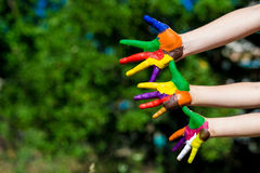 Child hands painted in bright colors  on summer nature background Stock Photography