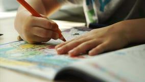 Child hands paints a orange pencils on a paper stock video
