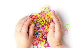 Child hands and pile of small colorful rubber bands Royalty Free Stock Photography