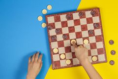 Child hands playing checkers on checker board game over yellow and blue background, top view. Child hands playing checkers on checker board game over yellow and stock images