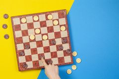 Child hands playing checkers on checker board game over yellow and blue background, top view. Child hands playing checkers on checker board game over yellow and royalty free stock photo