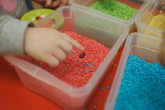 Child hands playing with colored rice in the sensory box. Baby`s sensory educational kit. Toddler hands playing with rainbow rice in the sensory box. Baby`s stock image