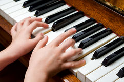 Child hands playing piano Stock Photos
