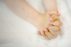 Child hands in prayer. A child's hands folded in prayer on white cloth Royalty Free Stock Photography
