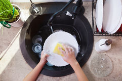 Child hands scrubbing a plate with sponge in the kitchen sink Royalty Free Stock Photography