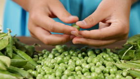 Child hands shelling peas stock video footage
