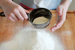 Child hands sifted flour. Royalty Free Stock Photo
