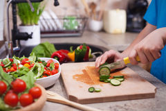 Child hands slicing a cucumber for a salad Royalty Free Stock Photos