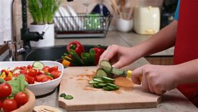 Child hands slicing a cucumber - side view. Child hands slicing a cucumber for a vegetables salad - side view of the cutting board at the kitchen sink stock footage