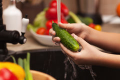 Child hands washing a cucumber at the sink, shallow depth Royalty Free Stock Image