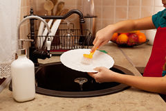 Child hands washing the dishes at the kitchen sink, shallow dept Stock Images