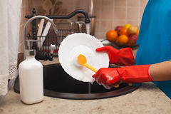 Child hands washing dishes - scrubbing a plate with a brush, sha Royalty Free Stock Images