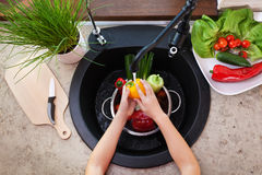 Child hands washing vegetables at the kitchen sink - a bellpeppe Royalty Free Stock Image