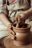 Child hands working on pottery wheel at workshop Stock Photos