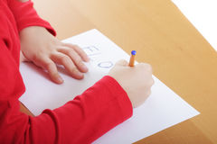 Child hands writing at desk Stock Photography