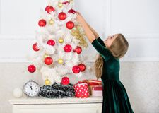 Child hang christmas ornament ball on artificial tree. Kids can brighten up christmas tree by creating their own royalty free stock images