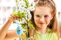 Child hang easter egg on cherry branch. Stock Photo