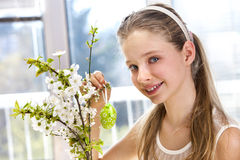 Child hang easter egg on cherry branch. Stock Photos