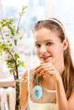 Child hang easter egg on cherry branch. Royalty Free Stock Photos