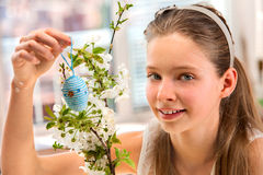 Child hang easter egg on cherry branch Royalty Free Stock Photos