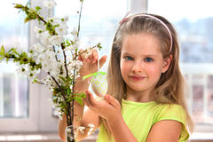Child hang easter egg on cherry branch Royalty Free Stock Image