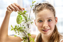 Child hang easter egg on cherry branch. Royalty Free Stock Image
