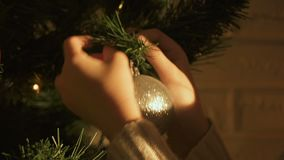 Child hanging bauble on Christmas tree, decoration for festive season, closeup. Stock footage stock footage