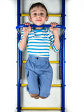 Child hanging on gymnastic equipment Royalty Free Stock Photography