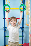 Child hanging on gymnastic rings. Child boy hanging on gymnastic rings at home Stock Photography