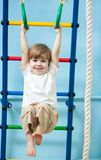 Child hanging on gymnastic rings Royalty Free Stock Photos