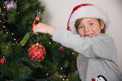 Child hanging up tree decorations Royalty Free Stock Photos